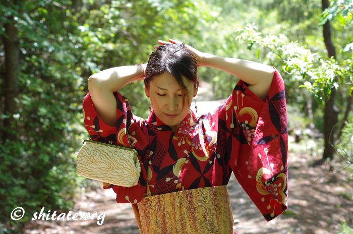 髪をかき上げる赤い浴衣女子