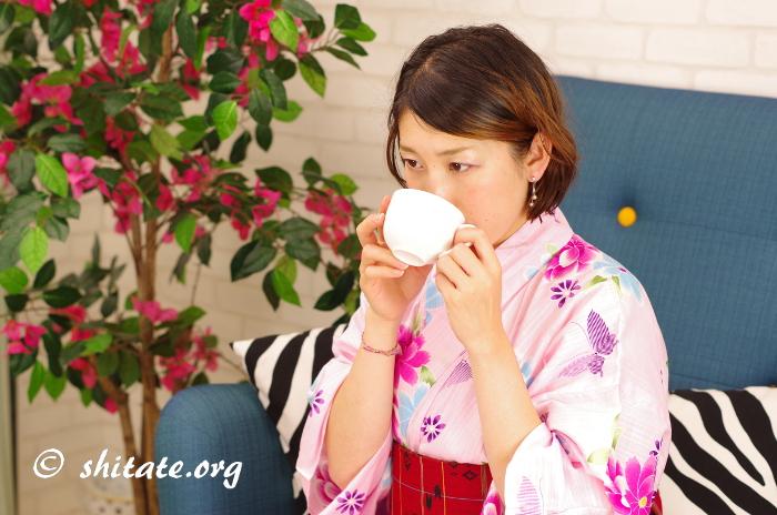 ピンクの浴衣で飲み物を飲む女子