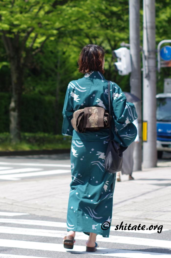 横断歩道を歩く深緑色の浴衣女性