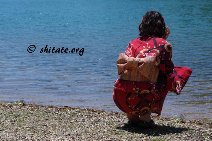 池の向こう側を眺める赤い浴衣女子