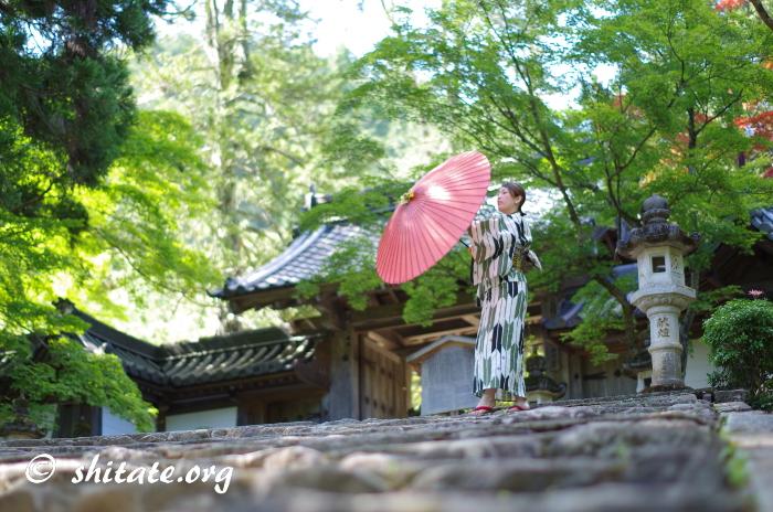 和傘を開こうとする浴衣女子