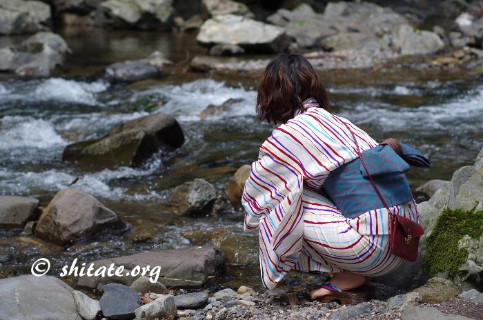 河原でしゃがみ込むモダン浴衣女子