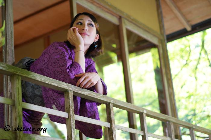 窓から顔を出す紫の浴衣女子