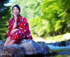川の上の岩で座る浴衣女子