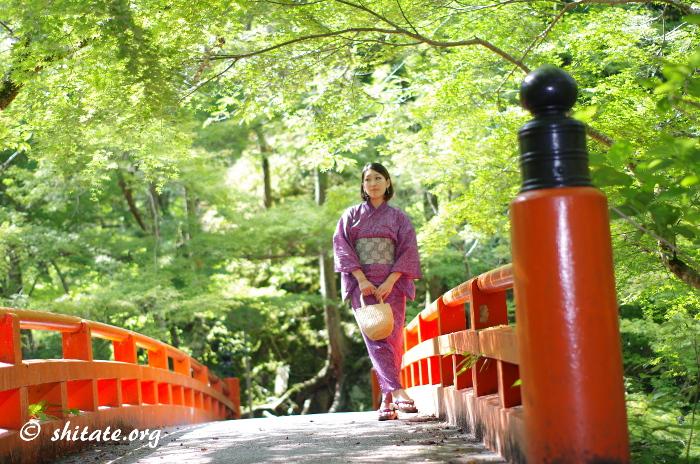 橋を渡る紫色の浴衣女性