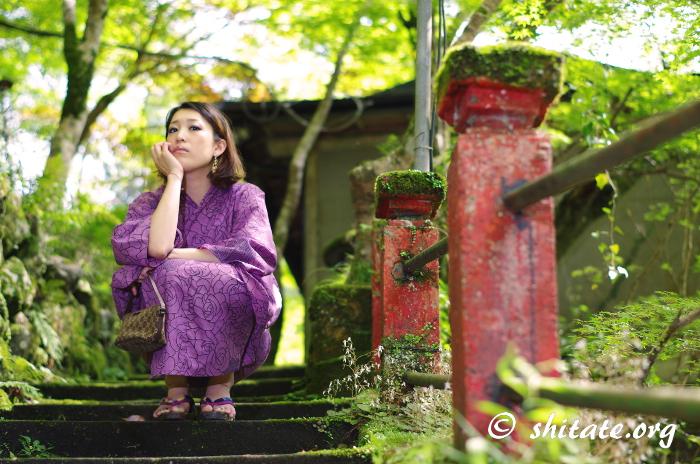 苔の階段で座る紫の浴衣女性