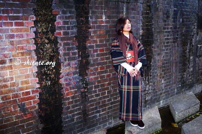 レンガの壁と普段着物な女性